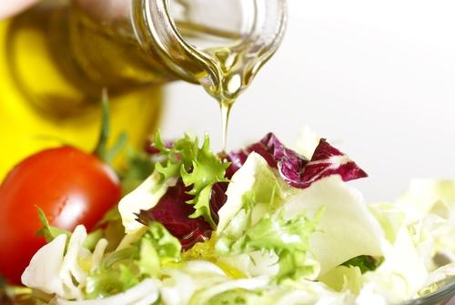 vertiendo-aceite-de-oliva-en-ensalada