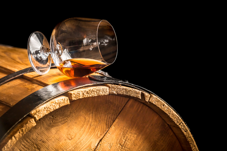 Glass of cognac on the vintage barrel